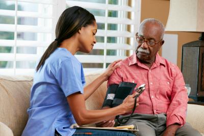 nurse checking her patient blood pressure