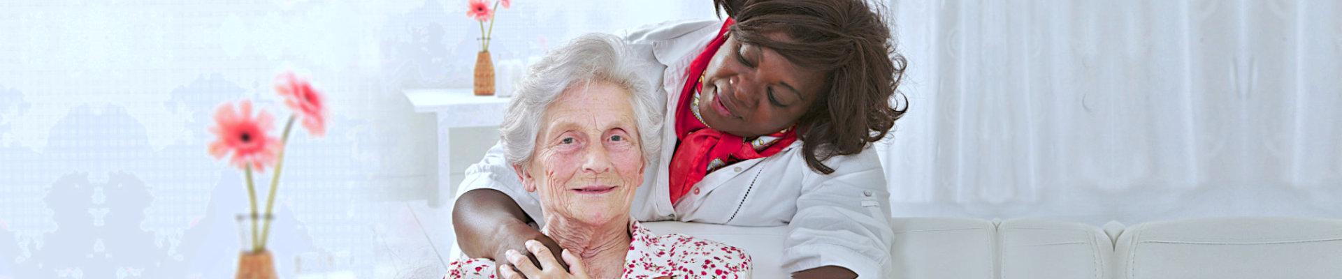 caregiver hugging a senior woman